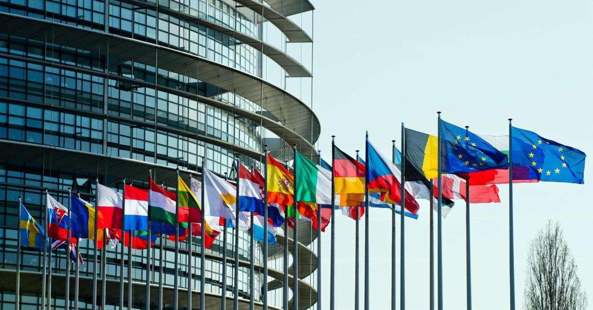 Vista esterna del Parlamento Europeo con le bandiere dei paesi appartenenti all'EU